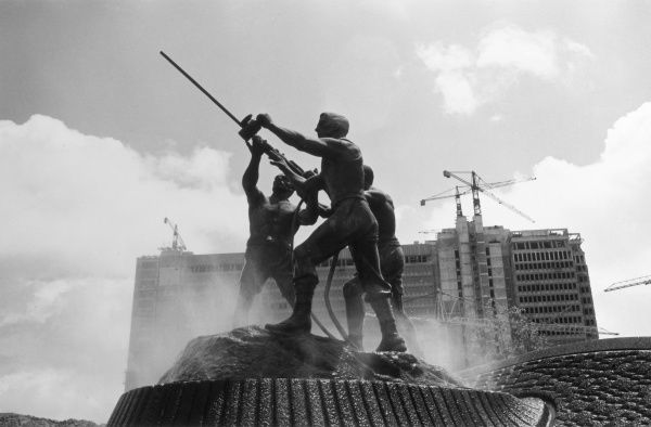 The famous Gold Mining Statue, Johannesburg, South Africa, depicting 3 men - 2 black and 1 white, drilling a rock face, a bronze sculpture by David McGregor, 1960. Date: 1960