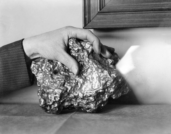 A nugget of gold, photographed with a hand to show its size. Date: 1930s