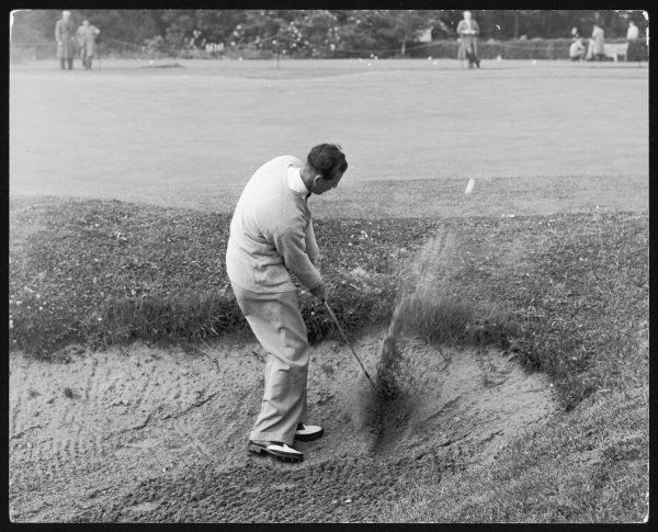 E.G. Lester plays from a bunker at Sunningdale, during the Daks golf tournament