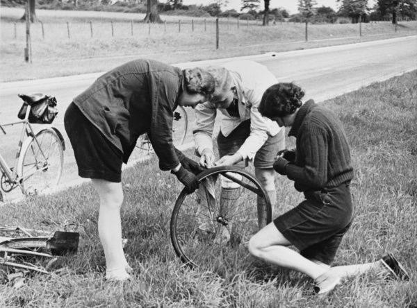 'The Helping Hand' : A male cyclist helps two distressed females to mend a punctured bicycle tyre