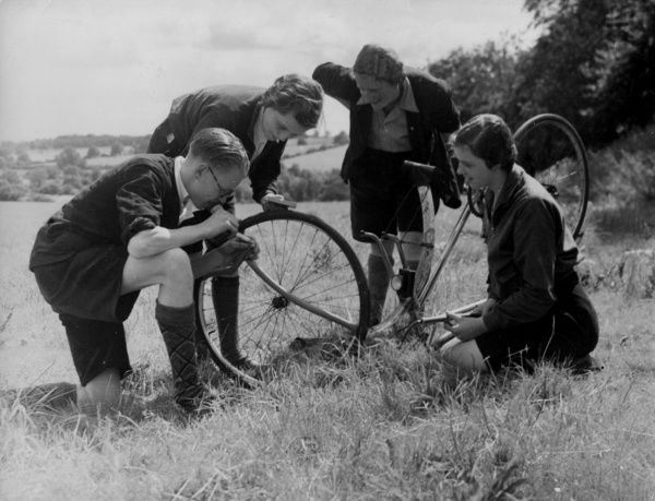 'The Helping Hand' : A male cyclist helps three distressed females to mend a punctured bicycle tyre! Date: 1930s