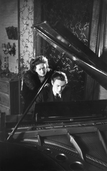A young woman watches over her partner's shoulder as he plays at a grand piano in a Gothic setting. Date: 1930s