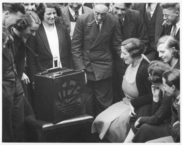 An excited audience listen to a broadcast of the Grand National (horse race) on the wireless