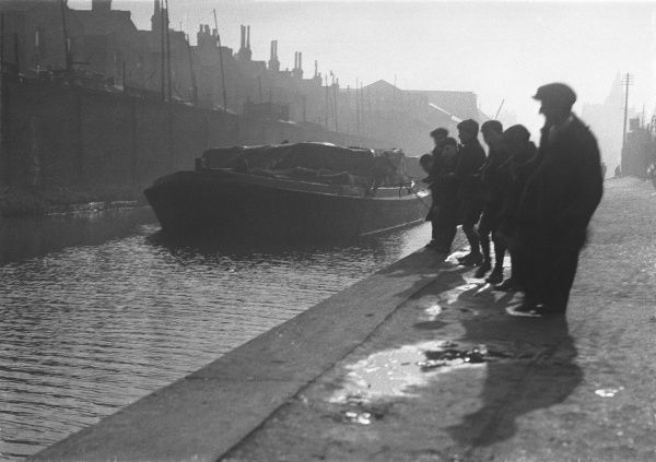 Workmen waiting in the morning sunshire for an industrial barge to reach them so that they can unload it, Peckham (London) branch of the Grand Surrey Canal, England