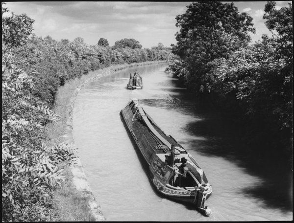 A Spring scene on the Grand Union Canal, near Bugbrooke, Northamptonshire, England, showing two laden narrow boats passing through the May blossom hedges along the way