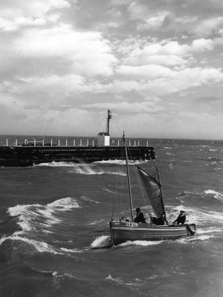 A 'shrimper' enters Great Yarmouth Harbour, Norfolk, England, in choppy waters. Date: 1950s