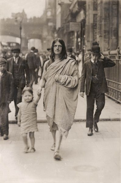 A Greek family living the simple life in London -- a Greek father walks along the street hand in hand with a small child, both of them dressed in rough sackcloth. More conventionally dressed Edwardians can be seen behind them
