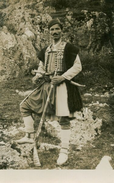 A Greek Gentleman wearing traditional costume, a splendid moustache and bearing a wide array of weapons on his person!
