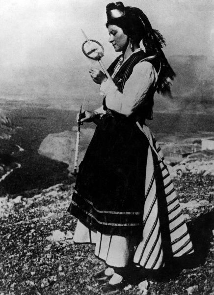 A Greek girl in traditional costume, using an old- fashioned spiining rod with her nimble fingers. Date: 1930s