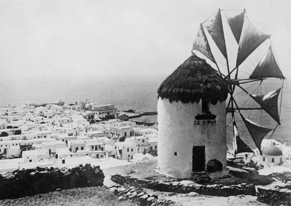 A typical windmill in Greece, with equally typical town of whitewashed or painted houses in the valley below. Date: early 1930s