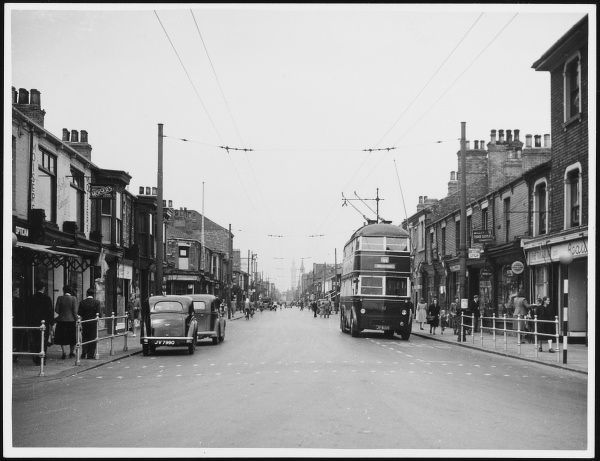 A trolleybus and only two cars on Freeman Street, Grimsby, Humberside. Note the smartly-dressed pedestrians and litter-free street