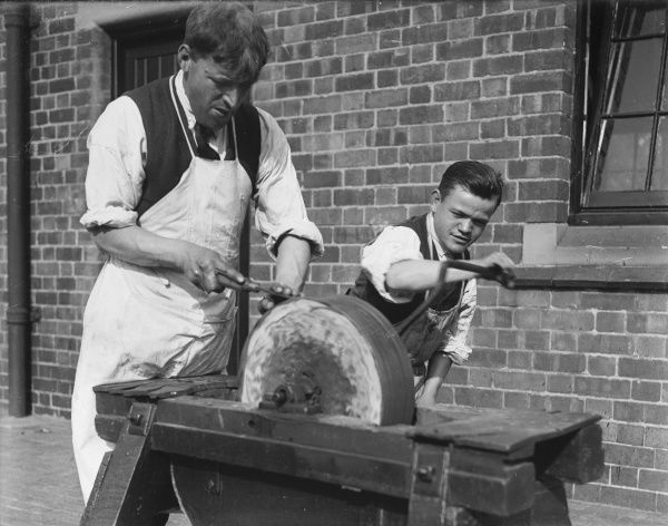 A grinder and his assistant sharpening knives or other tools on a grindstone