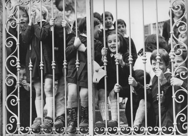 A happy group of children looking through their school gates, probably excited to be photographed. Their teacher smiles in the background on the right