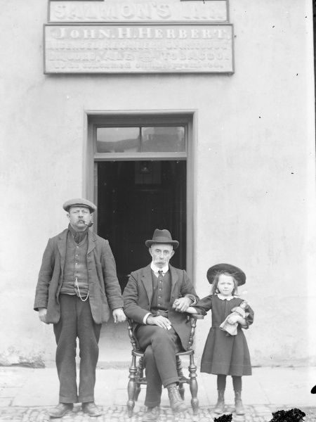 The Three Salmons Inn in the town of Crickhowell, Powys, Mid Wales, with two men and a girl with a doll posing for their photograph -- perhaps three generations of a family