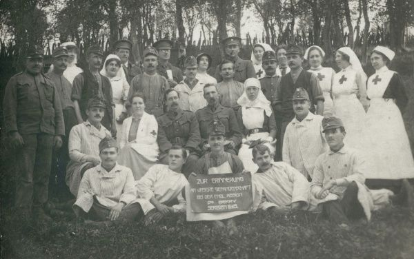 "A group photograph of Austrian prisoners and their nurses at Dr James Berry's Serbian Mission, a Red Cross Unit in Serbia during the First World War. The notice reads ""In memory of our captivity in the English Mission of Dr Berry, Serbia, 1915&quot"
