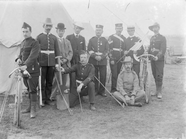 A group of soldiers and civilians at a training camp, posing for their photo outside a tent. The soldiers are dressed in a variety of uniforms, and two are holding bicycles, while one holds a spade