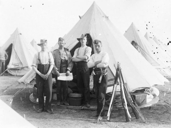 A group of four soldiers at a training camp, informally dressed, posing for their photo outside a tent. A stook of rifles can be seen on the right