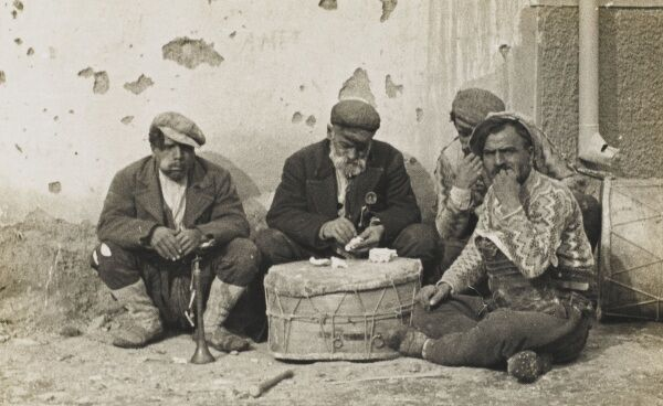 Group of Turkish street musicians eat bread served off a drum. In Turkey the principle constituent of every meal is bread, with meat or fish serving only as the adjunct