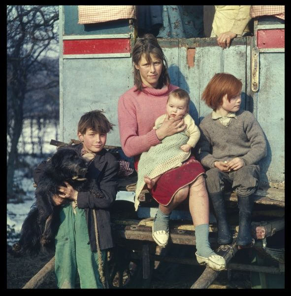 A gypsy family pose for a photograph on the step of their caravan at an encampment in Surrey