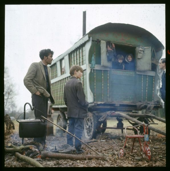 A Gypsy Father and son stand next to their green caravan as a large pot cooks above a basic fire. Two children peer out from within the caravan at this Surrey encampment