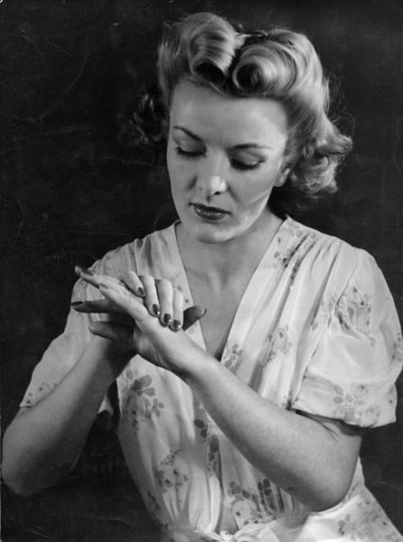 A stylish model rubs lotion into her lovely hands to keep them soft and supple. Date: early 1940s