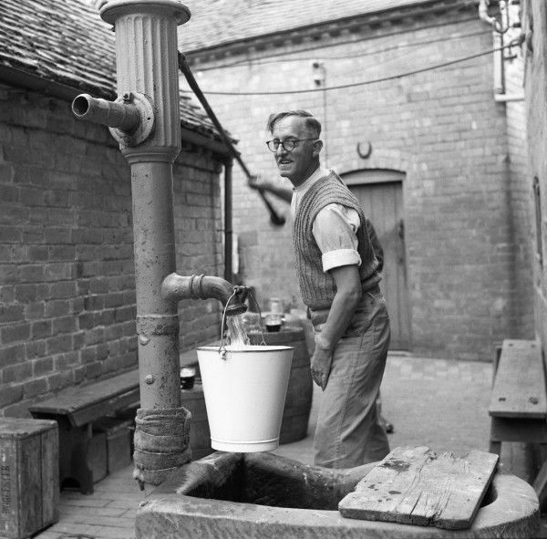 Operating a hand pump at the Fruiterer's Arms, Hartlebury, Worcestershire. Photograph by Norman Synge Waller Budd