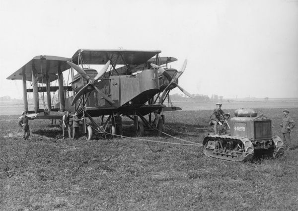 A Handley Page bomber with its wings folded, being moved into position for takeoff by a Clayton tractor on an airfield during the First World War. Date: 29 August 1918