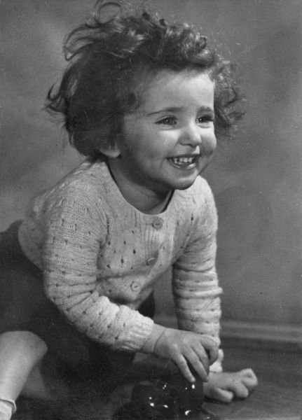 A happy little girl in a knitted cardigan, smiling broadly. She has short, curly hair and is playing with a shiny ornament