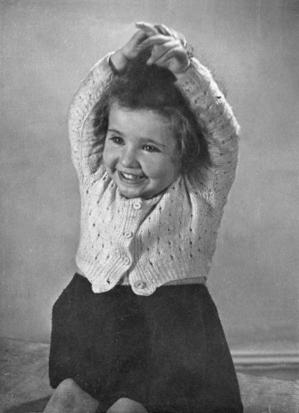 A happy little girl in a knitted cardigan, holding her hands above her head in delight. She has short, curly hair