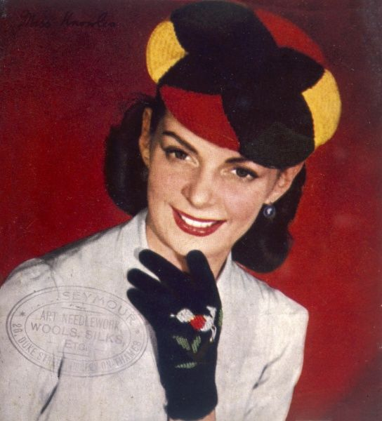 Smiling brunette in a 4 colour knitted hat and gloves with an embroidered robin