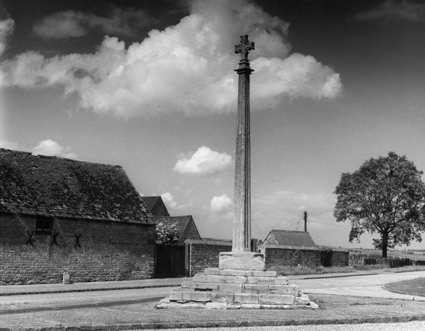The fine Market Cross, with its tall shaft, in the village of Harringworth, Northamptonshire, England. Date: 1950s