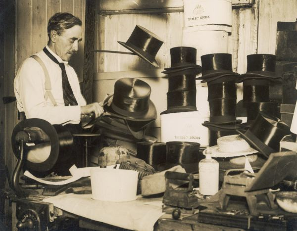 A variety of Harrow schoolboys' hats, including many top hats and straw boaters, are refurbished by the local hatter