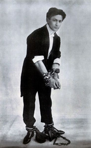 Harry Houdini, escapologist, with chains and padlocks around his wrists and ankles