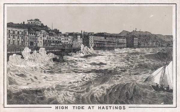 Rough waves pound the sea wall during high tide at Hastings. A small sailing boat is tossed by the swell