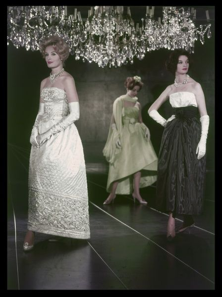 Three glamorous models adorn the catwalk, dressed in the latest satin and taffeta haute couture dresses. Note the huge chandelier above them