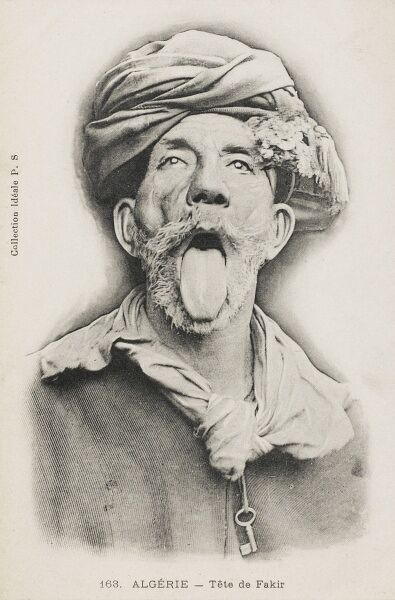 A superb (and very funny) photograph showing the head of an Algerian Fakir wearing a turban, with a chain round his neck and with his tongue sticking out!