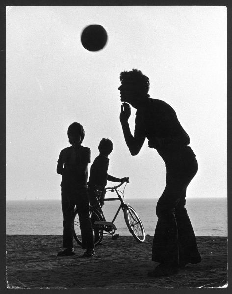 Silhouette of a teenager heading a football on a beach, watched by two smaller boys, one holding his bicycle