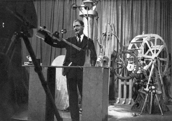 Photograph of William Heath Robinson (1872 - 1944), pictured with his own model of a pea-splitting machine. A well-loved artist, illustrator and cartoonist, Heath Robinson was known as the Gadget King due to the ridiculous contraptions he drew