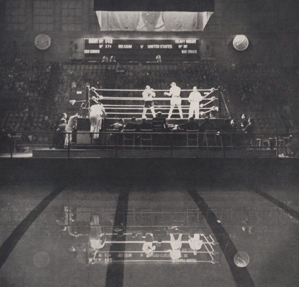 E.J. Lambert of the USA (right) and F. Bothy of Belgium competing for heavyweight honours at the Empire Pool (hence the reflection in the lower half of the photograph), where the Olympic boxing competitions were held. Date: 1948