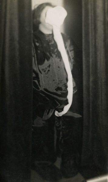 "Undated photograph of the Scottish medium Helen Duncan showing ""ectoplasm"" bunched around Duncan's mouth and twisted into a tail between her legs. HPG/1/4/2 (iv)"
