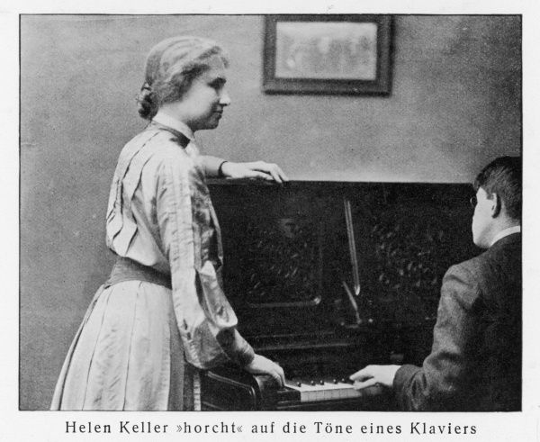 HELEN ADAMS KELLER (1880-1968), American author and lecturer who was left blind, deaf and mute at the age of 19 months, seen here listening to a piano