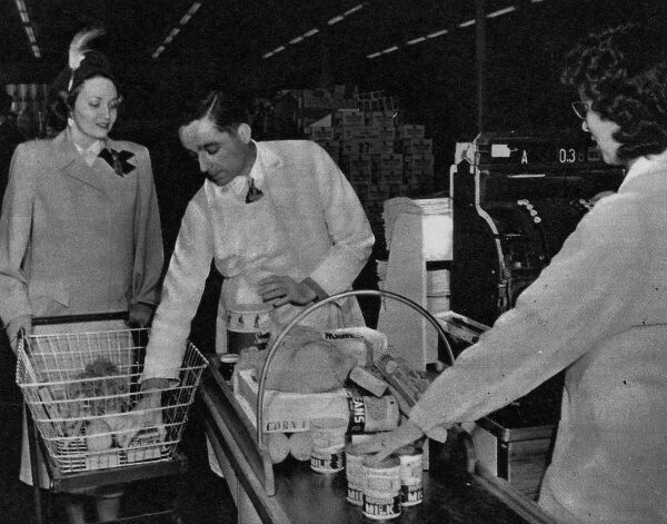 Photograph taken from a United States supermarket in 1948, 'where Britain's queues and rations are unknown', showing a woman being served at the checkout. The concept of the supermarket where all manner of goods could be bought in one place