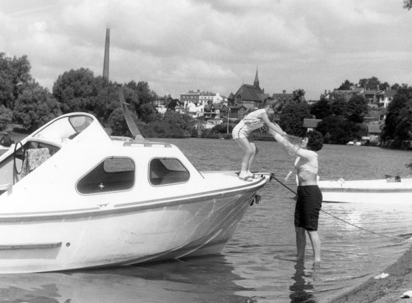 A helping hand - mother helps her young daughter to get down from a motor boat on the River Dee, Chester, Cheshire, England. Date: 1960s