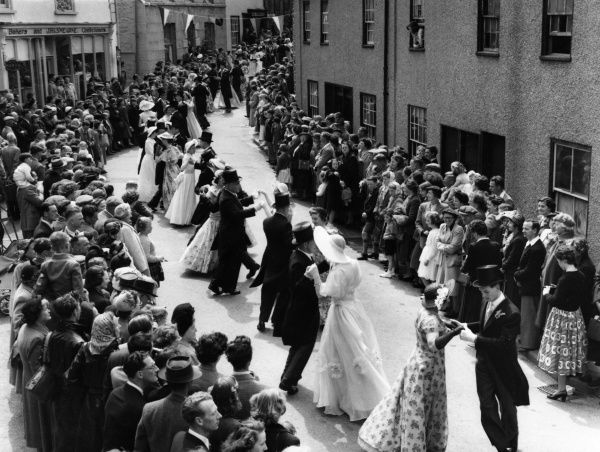 THE FLORAL DANCE takes place during Furry day at Helston, Cornwall, England. At noon, couples in evening wear dance between the houses to bring the occupiers good luck. Date: 1950s