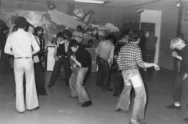 A group of boys wearing flared jeans, denim jackets and checked shirts play air guitar to a rock song at Helston youth club