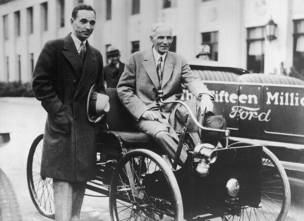 Henry Ford (1863 - 1947) and his son Edsel Ford (1893 - 1943) seated in the Quadricycle (1890s) alongside the 15,000,000th Ford produced