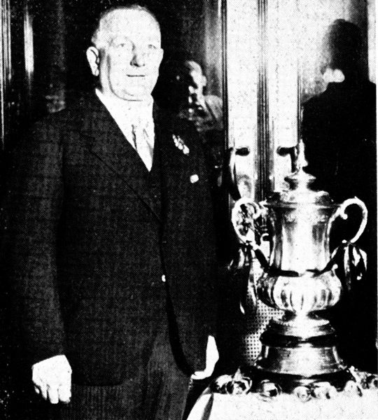 Photograph showing Herbert Chapman, Arsenal Football Club Manager between 1925 and 1934, standing beside the Football Association Cup Trophy. Chapman was one of Arsenal's finest ever managers, winning both the Football League and the FA Cup