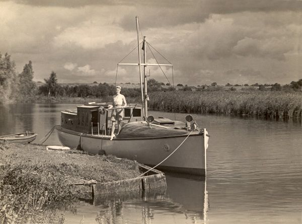 A woman stands on the deck of a boat which is moored at Hickling Broad on the Norfolk Broads in East Anglia during the 1930s