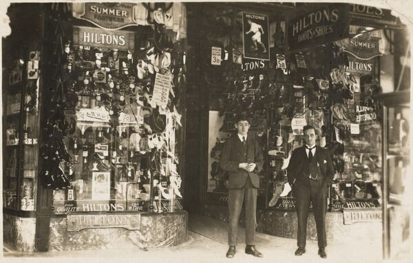 Hiltons Shoe Company. The Branch Manager and his young employee stand outside the shop, which has taken direct branding to a new level - preventing even the casual passer-by from ever forgetting the name of the store