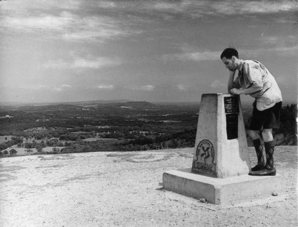 A young man wearing shorts and Argyll socks studies a National Trust stone on Hindhead Common, Surrey, England, which points out local places of interest. Date: 1930s